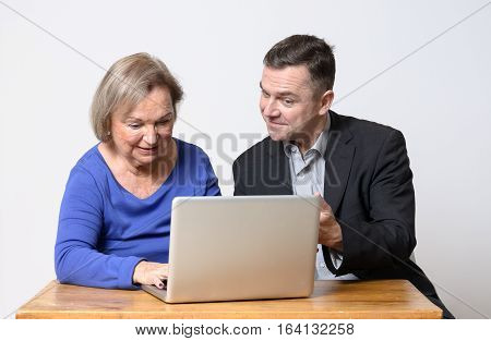 Senior Woman Using Computer Beside Man In Suit