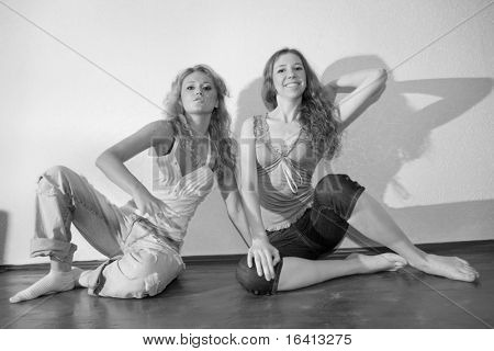 Schwarzweiß-Foto von zwei attraktiven jungen Frauen sitzen