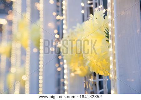 Close up of decoration yellow flowers decorated on white bower with defocused blurred lights bokeh background and copy space.