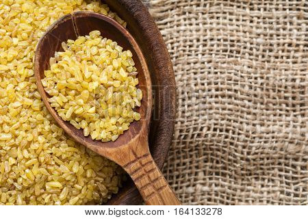 Bulgur, wheat grains. Raw uncooked bulgur in wooden spoon on linen textile background. Copy space for text. Healthy gluten free grains for cooking