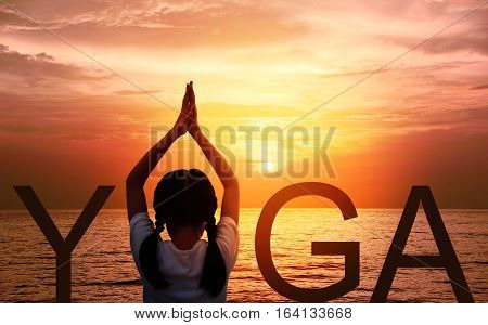 Silhouette of Young Asian girl doing Yoga vrikshasana tree pose on tropical beach with fantastic sunset sky background. Preteen girl or Kid standing as part of the word yoga sign and watching sunrise.