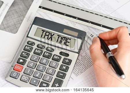 Tax form with pen, envelope and calculator saying tax time