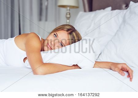 Beautiful Woman Lying On Her Bed At Home And Embraces The Pillow