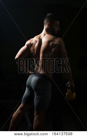Fitness Man Using Kettlebells Inside Gym