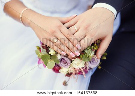 Hands of bride and groom with rings on wedding bouquet. Marriage concept