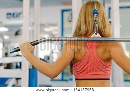 Close up photo of young girl working out on a fitness station in gym