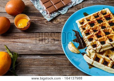 Homemade wafers on blue plate on wooden table with tangerines