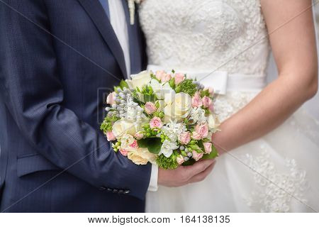 Bride and groom holding bright colourful wedding bouquet. Marriage concept
