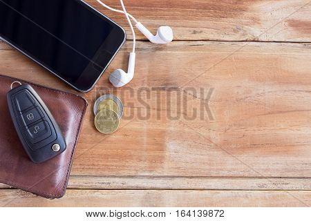 Smart phone wallet and car key on wooden table with ear phone. copy space