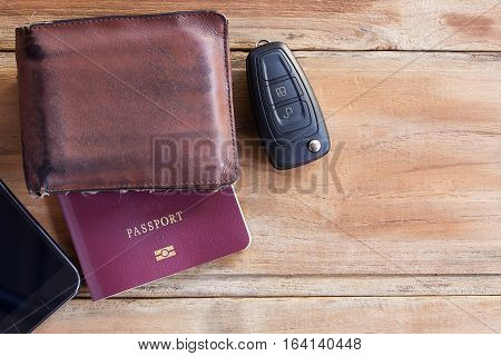 Smart phone, wallet, passport and car key on wooden table with ear phone. copy space