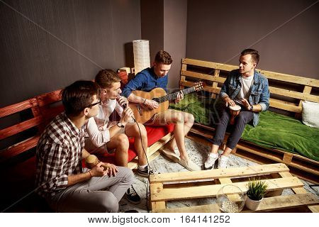 Group of Four Friends Hanging Out in Studio. Guys Singing and Playing Music in Urban Apartment. Toned Photo with Copy Space.
