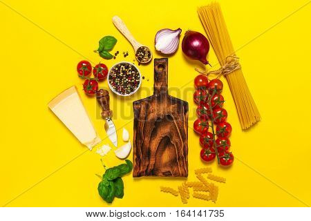 Italian food or ingredients background with fresh vegetables pasta cheese parmesan and spices. Top view view from above. Vibrant yellow background