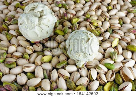Two scoops of Pistachio Ice Cream on Pistachios with copy space. Focus on ice cream scoop in the front. Shallow depth of field.