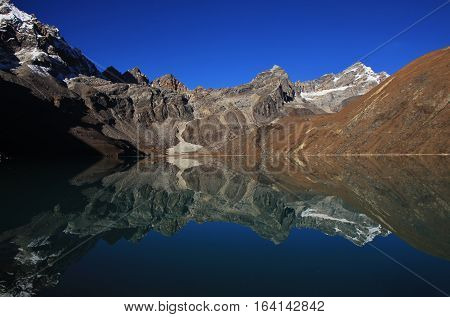 Autumn scene in the Everest National Park. View of the Renjo La mountain pass. Mirroring in Gokyo lake.