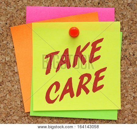 The words Take Care in red text on a yellow sticky note pinned to a cork notice board as a reminder