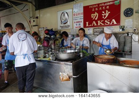 Hawker Vendor At Their Assam Laksa Noodle Stall In Air Itam, Penang