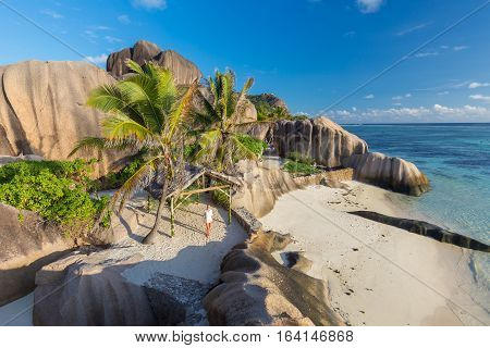 Female traveler emjoying amazing view of beautifully shaped granite boulders at picture perfect tropical Anse Source d'Argent beach, La Digue island, Seychelles.