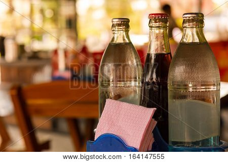 Water bottles and coca-cola bottle and Tissues on table and background restaurant in Asia.