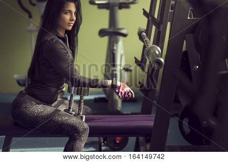 Attractive muscular young woman taking a break on workout in the gym sitting on a weightlifting machine