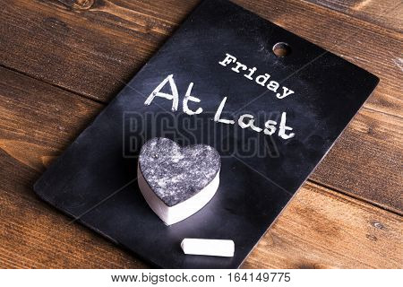 Friday at last notice on a chalk board with chalk and heart shaped eraser. Concept of working people pleased to make it thought the week and get to the weekend. Background set on a rustic wooden boards