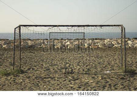 Empty football field and goal posts with broken nets on the beach.