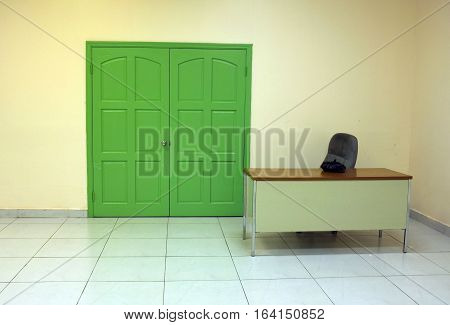 Deserted work post in an office building with empty desk and closed green double doors.