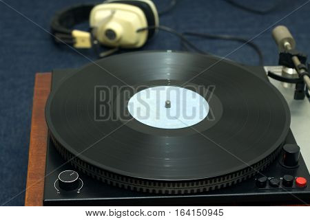 Analogue sound reproduction from vintage classic style old school turntable in wooden case with vinyl record and headphones. Horizontal photo front view closeup