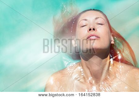 Enjoy the summer. Woman relaxing in the pool water. A beautiful woman floating in water in a swimming pool. Relaxation and peace. Eyes closed and wellness enjoyment in the summer.