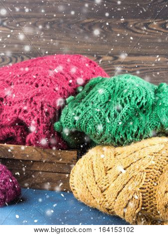 Winter womans woolen sweaters. Knitted girls clothing. Colorful pullovers on wooden background. Cozy clothes for the season.
