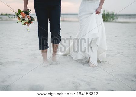 Bride and groom walk on the beach. Cropped image