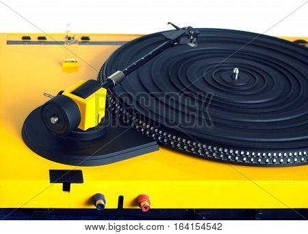 Turntable with black tonearm in yellow case with rubber mat on disc with stroboscope marks with output connectors rear view isolated on white background rear view closeup