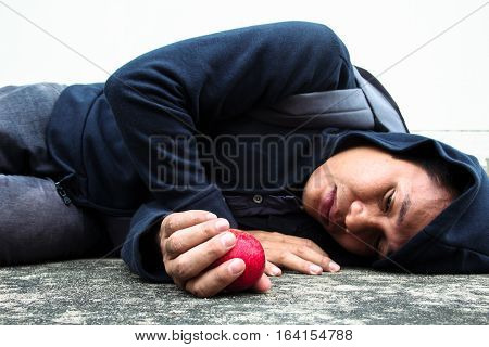 Homeless person lay down on the floor with an apple in hand,showing what left in life after face a problem