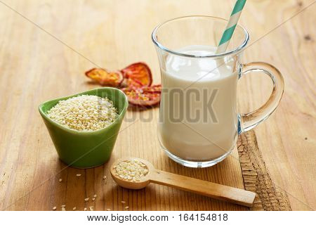 Sesame seed milk in a glass. White sesame seeds on a table. Raw food diet.