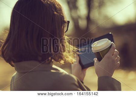 Woman on a coffee break sitting in a park, reading online news and drinking coffee
