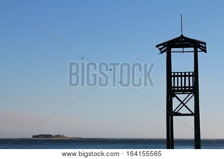 Silhouette of wooden watchtower with sky and sea background.