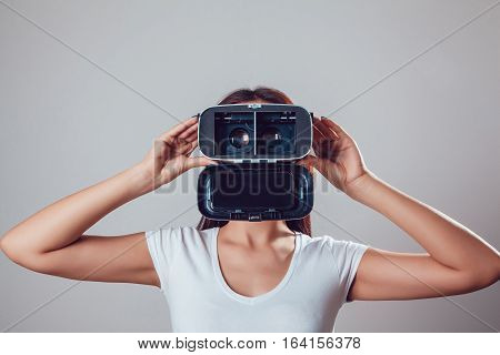 Attractive woman wearing virtual reality goggles. VR headset. Virtual reality concept on grey background.