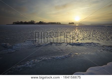 Winter landscape with river and sunset sky. Composition of nature.
