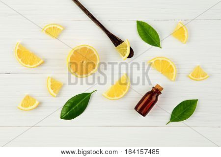 Fresh Lemons And Leaves With Essential Oil On Rustic Wooden Background. Fresh  Lemon Slice And Essen