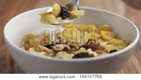 closeup eating with a spoon breakfast with corn flakes and mix of nuts and fruits, 4k photo