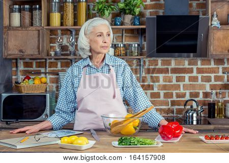 Senior woman in apron standing at kitchen table with ingredients and looking away