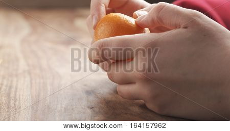 young female hand peels clementine tangerine on wooden table, 4k photo