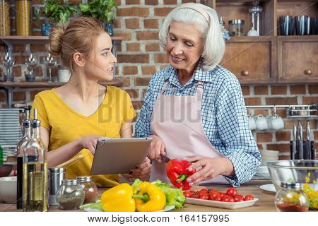 Granddaughter and grandmother using digital tablet while cooking vegetable salad together