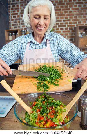 Smiling senior woman cutting salad greens at kitchen