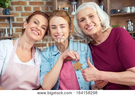 Happy family of three generations smiling and looking at camera. Senior woman showing thumb up