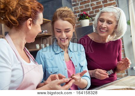 Happy family of three generations preparing gingerbread cookies at home