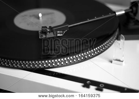 Turntable in silver case playing a vinyl record with red label. Black and white photo side view closeup