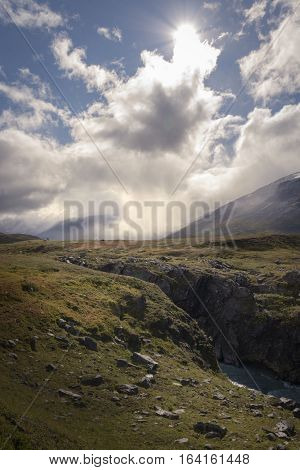 Small lonely hiker standing in enormous cloud and sunlight covered autumn wilderness