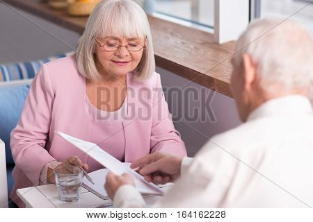 Let us figure this out. Enthusiastic beautiful aged lady giving detail on some points of the contract to her companion while sitting at the table and looking through her notes