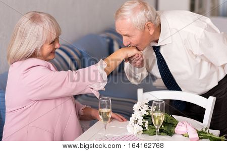 Very gentle. Gallant handsome senior man greeting his lady by kissing her hand while she timidly sitting at the table in a restaurant