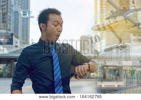 Young business man checking the time on his watch. time planes trains